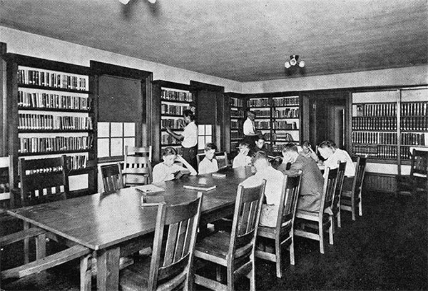 boys sit around a table reading, surrounded by shelves full of books